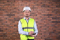 Male industrial engineer in uniform with clipboard on brick wall background. stock photo