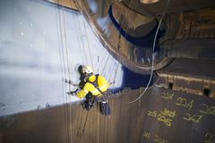 Male industrial rope access technician painter working at height hanging on twin ropes. Male rope access technician painter working at height hanging on twin stock photo