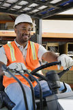 Male Industrial Worker Driving Forklift At Workplace. Happy African American male industrial worker driving forklift at workplace Royalty Free Stock Photo