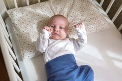 Male infant play in bed. Cute baby boy lying in bed, four month old Stock Image