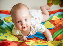 Male infant playing. On his soft colorful blanket with jungle animals Royalty Free Stock Photos