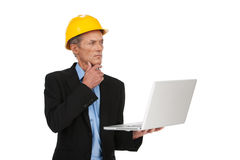 Male inspector in helmet working on computer. Royalty Free Stock Photo
