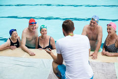 Male instructor assisting senior swimmers at poolside Royalty Free Stock Photography