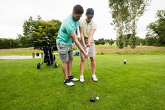 Male instructor assisting woman in learning golf Royalty Free Stock Photos