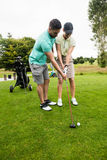 Male instructor assisting woman in learning golf Royalty Free Stock Images