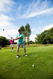 Male instructor assisting woman in learning golf Stock Photos