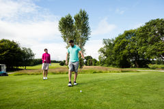 Male instructor assisting woman in learning golf Royalty Free Stock Photo