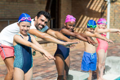 Male instructor and children preparing for jumping in swimming pool. Portrait of male instructor and children preparing for jumping in swimming pool Stock Photography