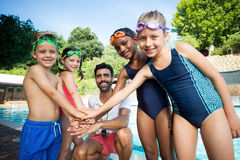 Male instructor and children stacking hands at poolside. Portrait of male instructor and children stacking hands at poolside Royalty Free Stock Photo