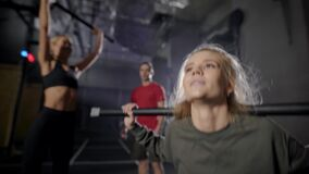 Male instructor is controlling workout of two sexy women in gym, ladies are lifting rods and squatting