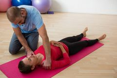 Instructor guiding female student in exercising at yoga studio. Male instructor guiding female student in exercising at yoga studio Royalty Free Stock Image
