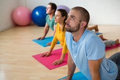 Instructor guiding students in practicing cobra pose at yoga studio Stock Photos