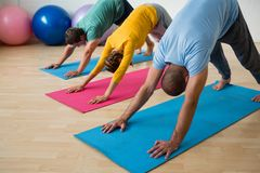 Instructor guiding students in practicing downward facing dog pose at yoga studio Stock Image