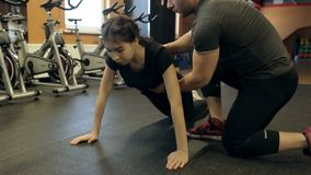 Male instructor is holding young sportswoman during the exercise in modern gym. Brunette sportswear is doing knee push-ups on the floor in power zone and stock footage