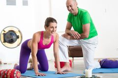 Male instructor looking at smiling woman doing exercise. Healthy male instructor looking at smiling women doing exercise in yoga class royalty free stock images