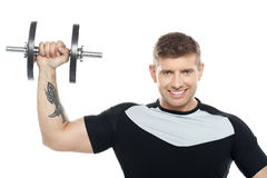 Male instructor posing with raised dumbbell Stock Photography
