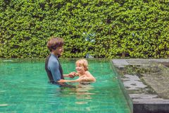 Male instructor swimming for children teaches a happy boy to swi. M in the pool Stock Photo