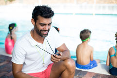 Male instructor watching stopwatch by children at poolside Royalty Free Stock Photo