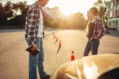 Instructor and woman, lesson for novice drivers. Male instructor and women student on lesson for novice car drivers, driving school concept. Test for beginner royalty free stock photography