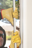 Burglar breaking through window of home. Male intruder with black hood, gloves and sunglasses trying to break in residential house, home, through window, with stock photography
