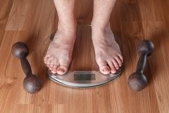 Male its feet on scales, and near lie two dumbbells royalty free stock photo