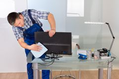 Male janitor cleaning computer in office. Portrait Of Happy Male Janitor Cleaning Computer On Office Desk Stock Photo