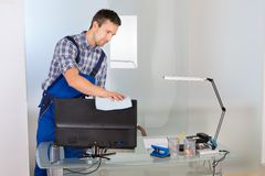 Male janitor cleaning computer in office Royalty Free Stock Image