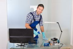 Male janitor cleaning desk Royalty Free Stock Photos