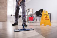Male Janitor Cleaning Floor In Office. Low Section Of Male Janitor Cleaning Floor With Caution Wet Floor Sign In Office stock photos