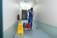 Male Janitor Cleaning Floor. Portrait Of Young African Male Janitor Cleaning Floor In Corridor Royalty Free Stock Photo