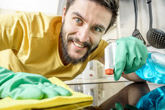 Male janitor cleaning kitchen with sponge. Male janitor cleaning kitchen with detergent spray bottle and sponge stock images