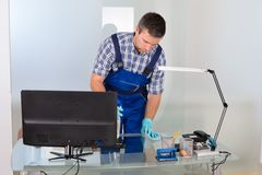 Male janitor cleaning office. Portrait Of Male Janitor Cleaning Desk In Office Stock Image