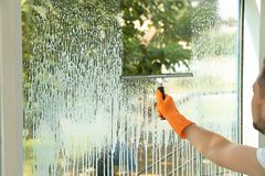 Male janitor cleaning window with squeegee. Closeup Stock Photography