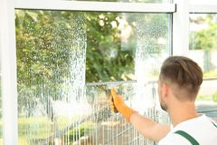 Male janitor cleaning window with indoors. Male janitor cleaning window with squeegee indoors Royalty Free Stock Photos