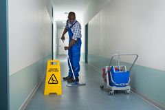 Male Janitor Mopping In Corridor. Young African Male Janitor Cleaning Floor In Corridor Royalty Free Stock Images