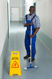 Male Janitor Mopping In Corridor. Young African Male Janitor Cleaning Floor In Corridor Stock Photo