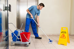 Male Janitor Mopping Floor Royalty Free Stock Photos