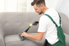 Male janitor removing dirt from sofa with cleaner. Male janitor removing dirt from sofa with upholstery cleaner indoors royalty free stock photos