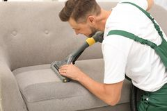Male janitor removing dirt from sofa. With upholstery cleaner indoors stock photo