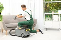 Male janitor removing dirt from sofa. With upholstery cleaner in room stock photography