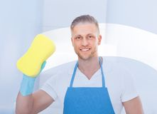 Male janitor using a sponge to clean a window. In an office wearing an apron and gloves as he works Royalty Free Stock Photo