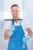 Male janitor using a squeegee to clean a window. In an office wearing an apron and gloves as he works Royalty Free Stock Photography