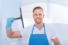 Male janitor using a squeegee to clean a window. In an office wearing an apron and gloves as he works Stock Photography