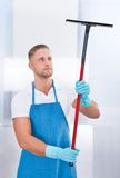 Male janitor using a squeegee to clean a window. In an office wearing an apron and gloves as he works Royalty Free Stock Image