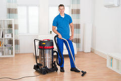 Male Janitor Vacuuming Floor. Happy Male Janitor Vacuuming Wooden Floor In House Royalty Free Stock Photos