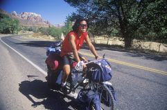 Male Japanese tourist bicycling in Zion National Park, Utah Stock Photography