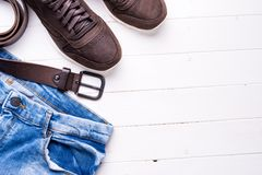 Male jeans, belt and shoes with text space. Male jeans, belt and shoes on wooden background with text space, top view Stock Photography