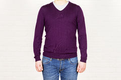 Male in jeans and purple shirt. On white brick background. Mock up Stock Photography
