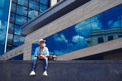 Male in jeans and shirt enjoying city while drinking coffee. Wide shot of male in jeans and shirt enjoying city while drinking coffee and sitting under Royalty Free Stock Photography