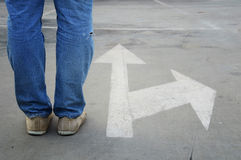 Male with jeans and white direction arrow. Male sneakers with jeans on the tarmac road with white direction arrow, concept of making decision at the crossroad Stock Photography